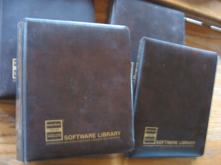 Software Library -- TRS-80; 4 softsided binders containing manuals and some cassette tapes. tandy corporation Radio Shack.